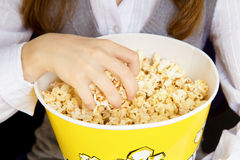 Hand in a bucket of popcorn. Child's hand in a bucket of popcorn royalty free stock photos