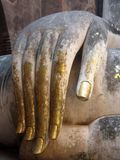 Hand of the Buddha image with gold leaves attached stock photography