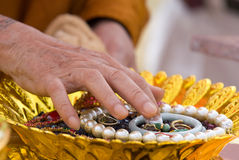 Hand of Buddhist monk painting religious symbols. On amulets with his finger. Shallow depth of field royalty free stock image