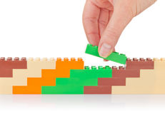 Hand build wall of colour toy block. On white background Royalty Free Stock Images