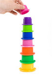 Hand building multicolor tower. Hand finishing a stacking cups tower Royalty Free Stock Photo