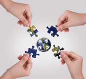 Hand building puzzle globe. Royalty Free Stock Photo