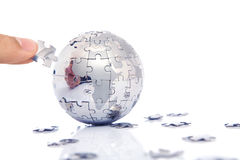 Hand building puzzle globe together Stock Photography