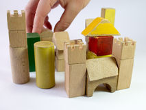 Hand building a toy wooden castle Royalty Free Stock Image