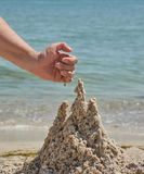 Hand builds a castle from the wet sea sand on the beach. On a summer day stock image