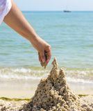 Hand builds a castle from the wet sea sand. On the beach on a summer day stock photo