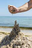 Hand builds a castle from the wet sea sand. On the beach on a summer day stock images
