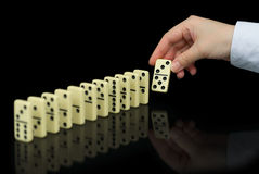 Hand builds a line of dominoes on black background Royalty Free Stock Photos