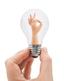 Hand with bulb and OK sign Stock Image