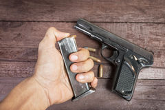 Hand with bullet and Semi-automatic 9mm gun on wooden background.  Royalty Free Stock Image
