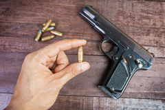 Hand with bullet and Semi-automatic 9mm gun on wooden background.  Royalty Free Stock Photo