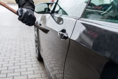 Crowbar on door lock on car stock images