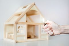Hand with burning lighter against wooden house model on the background. Arson of house concept. Criminal accident Royalty Free Stock Image