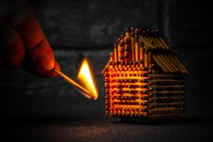 Hand with a burning match sets fire to the house model of matches, risk, property Insurance protection or ignition of combustible. Materials concept royalty free stock photography