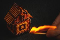 Hand with a burning match sets fire to the house model of matches, risk, property Insurance protection or ignition of combustible. Materials concept stock image