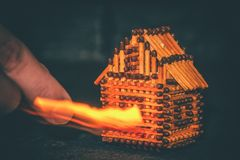 Hand with a burning match sets fire to the house model of matches, risk, property Insurance protection or ignition of combustible. Materials concept royalty free stock photo