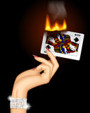 Hand with a burning playing card Stock Photos