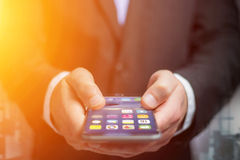 Hand of a business man holding black smartphone with operating s. View of a Hand of a business man holding black smartphone with operating system screen Stock Photography