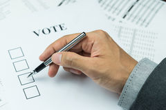 Hand of business man. Holding a pen trying to vote in paper Royalty Free Stock Photography