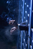 Hand of business man smoking. In jail with copyspace background Royalty Free Stock Image