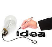 Hand of business man writing idea with light bulb beside Stock Images