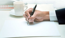 Hand of business man writing by pen on empty white papeer ,top t Royalty Free Stock Image
