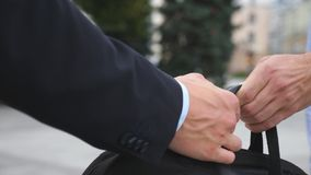 Hand of business man passing a black briefcase to his partner. Colleagues shake arms outdoor with blur city at. Hand of business men passing a black briefcase to Royalty Free Stock Image