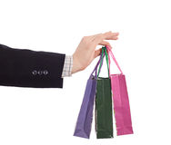 Hand of Business Style dressed Man holding small shopping Bags royalty free stock photography
