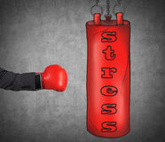 A hand in business suit is hitting the red punching bag. Royalty Free Stock Photo