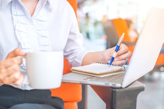 The hand of a business woman writing with a pen in notepad in th Royalty Free Stock Photography