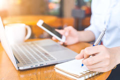 The hand of a business woman writing with a pen in notepad and w Royalty Free Stock Image