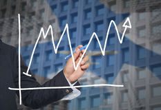 Hand of businessman drawing graphics a top point growing graph t Royalty Free Stock Images