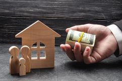 The hand of a businessman extends money to a wooden house. The family is standing near the house. The concept of buying and housing. Compensation and Stock Images