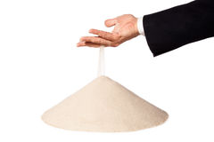 Hand of businessman with falling sand on pile Royalty Free Stock Photos