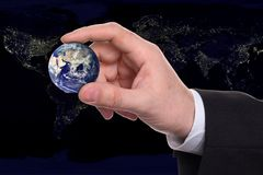 Hand of businessman with globe. Hand of businessman with world globe. Illuminated city lights in background Stock Images