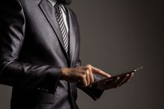 Hand of businessman in grey suit holding and touching application,Checking the growth rate of the stock market.on mobile phone royalty free stock images