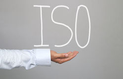 Hand of businessman and hand drawn text ISO system. Royalty Free Stock Photography