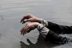 Businessman was arrested by handcuffs and drowning. Hand of a businessman handcuffed over water Stock Images