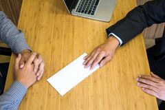 Hand of a businessman hands over a resignation letter final remuneration to executive boss on a wooden table to his boss Change of. Job, unemployment concept stock image