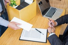 Hand of a businessman hands over a resignation letter final remuneration to executive boss on a wooden table to his boss Change of. Job, unemployment concept stock photography