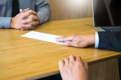 Hand of a businessman hands over a resignation letter final remuneration to executive boss on a wooden table to his boss Change of. Job, unemployment concept royalty free stock photography