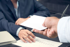 Hand of a businessman hands over a resignation letter. On a wooden table stock photo