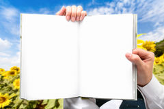 Hand businessman holding book outdoor green fields. Royalty Free Stock Image
