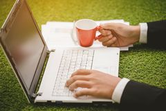 Hand businessman holding coffee  cup and using laptop o. Close up hand businessman holding coffee cup and using laptop on green grass Stock Photo
