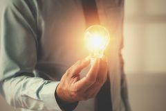 Hand businessman holding light bulb, innovation and inspiration Royalty Free Stock Image