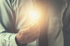 Hand businessman holding light bulb, innovation and inspiration Stock Image
