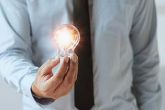 Hand businessman holding light bulb, innovation and inspiration Royalty Free Stock Photo