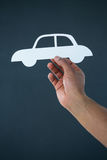 Hand of businessman holding paper cut out car Royalty Free Stock Photo