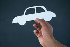 Hand of businessman holding paper cut out car Royalty Free Stock Images