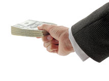Businessman holding pile of dollars. Hand of businessman holding pile of dollars Stock Image